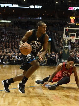 Bucks forward Khris Middleton drives to the basket as Raptors guard DeMar DeRozan falls to the ground in the first half of Milwaukee's Game 3 victory over Toronto on Thursday night at the BMO Harris Bradley Center.
