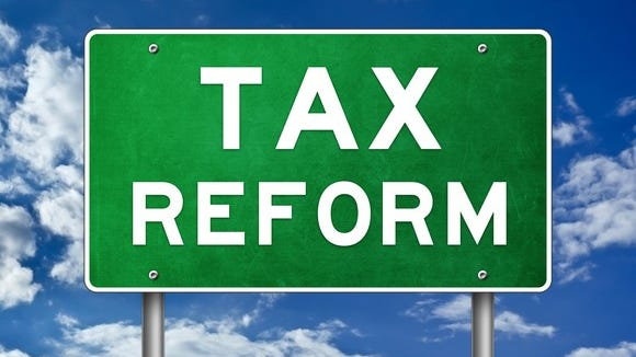 A green highway sign that reads tax reform, with a blue sky in the background.
