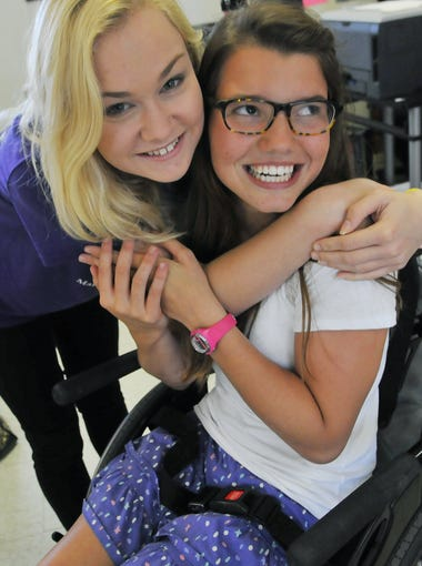 Seventeen-year-old Olivia DeBoer gets a hug from 15-year-old Tiffany Dion at Cocoa Beach Jr. / Sr. High.
