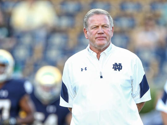Notre Dame Fighting Irish head coach Brian Kelly stands on the field prior to a game against the Michigan State Spartans at Notre Dame Stadium.