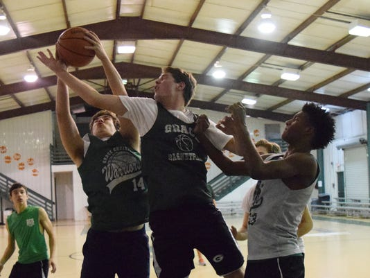 Grace Christian players Noah Dufour (left), Micah Couvillion and DeMarcus Hall go after a rebound at a practice held Tuesday.