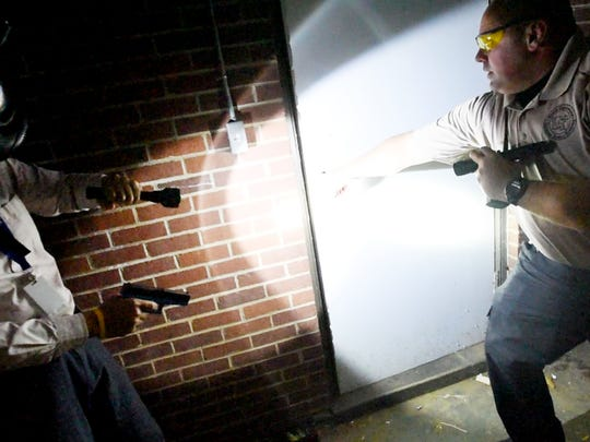 Times reporter Miles Jay Oliver takes instructions on clearing a door in the shooting simulation Wednesday night.