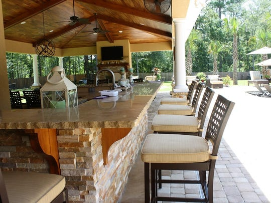 The stacked stone wraps around an L-shaped bar held up by wooden corbels that match a stunning ceiling.