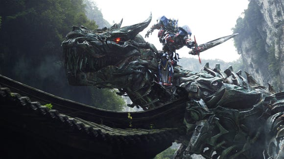 Optimus Prime rides the Dinobot named Grimlock in 'Transformers: