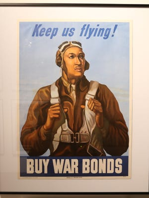 """A buy war bonds poster which is part of fthe FDR Presidential Library & Museum's exhibit """"The Art of War"""" on April 19, 2018. This particular poster by Betsy Graves Reyneay is one of the few examples of posters that focused on the African American community, and was inspired by Robert W. Diez, a Tuskegee Airman."""