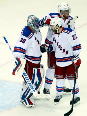 New York Rangers goalie Henrik Lundqvist (30) celebrates with defenseman Marc Staal (18) and defenseman Dan Boyle (22) after game four of the Eastern Conference Final of the 2015 Stanley Cup Playoffs against the Tampa Bay Lightning at Amalie Arena.