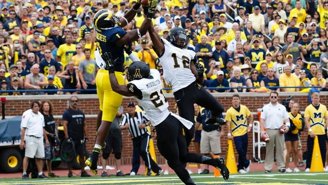 Michigan wide receiver Devin Funchess (87) makes a catch for one of his three touchdowns, over Appalachian State defensive backs, Doug Middleton (21) and Jordan Ford (12), in the second quarter Saturday at Michigan Stadium.