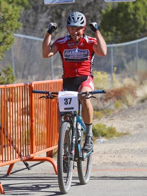 Brent Winebarger celebrates after crossing the finish line on Saturday during the Road Apple Rally at Lions Wilderness Park in Farmington.