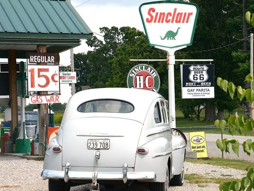 """An old Ford sits in the restored Gay Parita Sinclair gas station on Route 66 in Paris Springs. A """"gas war"""" sign is showing the price per gallon to be a mere 15 cents."""