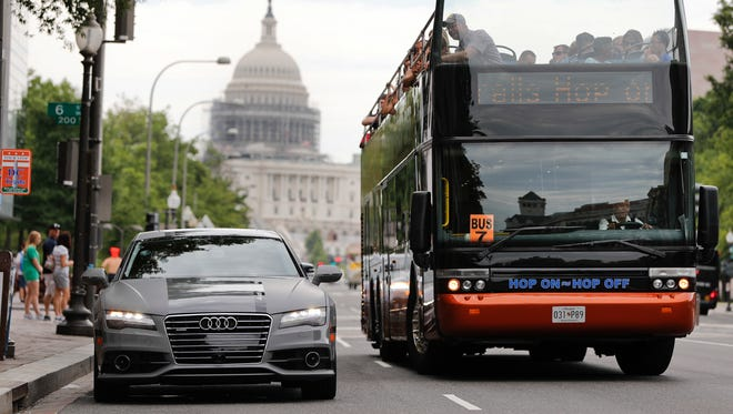 A double decker tour bus drives by an Audi self driving vehicle parked on Pennsylvania Avenue, near the Capitol in Washington.