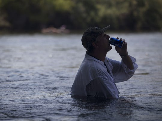 A man keeps cool sitting in the Salt River on Saturday,