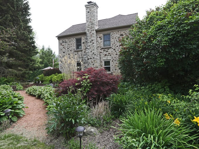 A landscaped garden surrounds one side of the farmhouse.