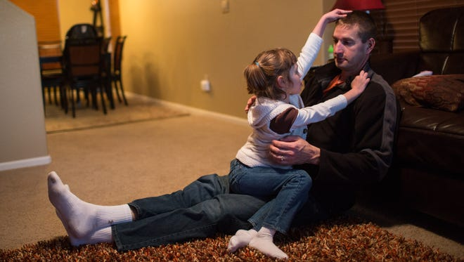 Mark Botker plays with daughter Greta, 7, at their new Colorado home. Greta is prescribed cannabis oil for severe seizures. The oil is extracted from a genetically modified strain of marijuana called Charlotte's Web.