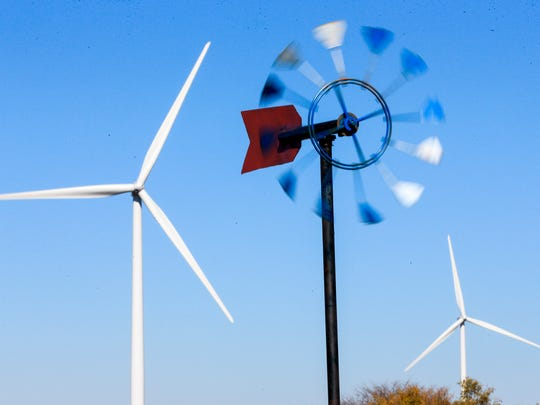 An ornamental windmill spins in front of wind turbines near Steele City, Neb.