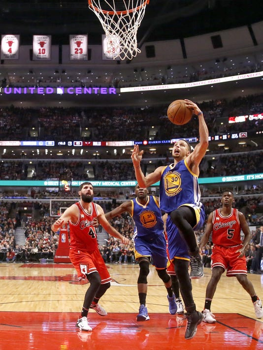 Golden State Warriors guard Stephen Curry (30) drives past Chicago Bulls forward Nikola Mirotic (44) and Bobby Portis (5) as Festus Ezeli watches during the second half of an NBA basketball game Wednesday, Jan. 20, 2016, in Chicago. Warriors won 125-94. (AP Photo/Charles Rex Arbogast)