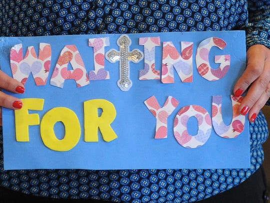 Ronda Haston, Indianapolis, holds a sign that expresses her feelings as she waits for her adopted child.