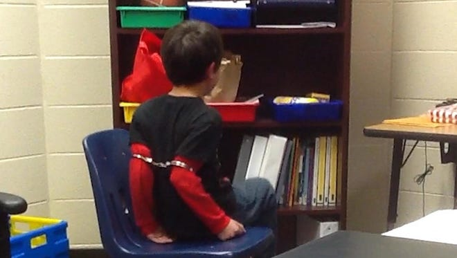This image from video shows an 8-year-old Covington student in handcuffs around his arms.