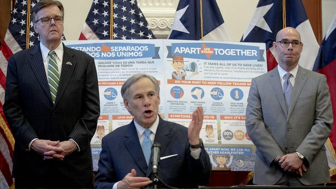 Texas Gov. Greg Abbott, flanked by Lt. Gov. Dan Patrick, left, and House Speaker Dennis Bonnen, speaks during a March 31 press conference at the state Capitol about the state's response to the coronavirus.