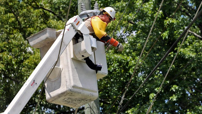 Chris Anderson from City of Shelby works to restore power to Shelby after a large tree fell on lines on Wednesday.