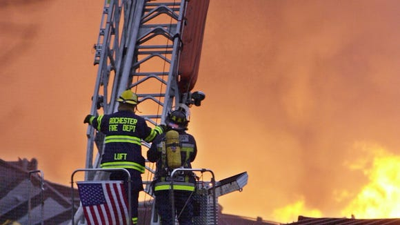 Two Rochester firefighters stand on a ladder as the fire, which started from a CSX train derailment, is brought under control at the Stutson Street bridge on River Street.