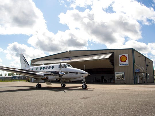 A Beachcraft King Air airplane is parked outside one