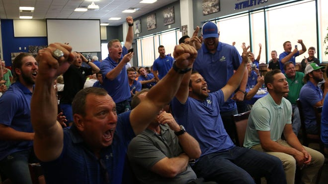 Founding head coach Dave Tollett, left, and the FGCU baseball team react to hearing its name called during an NCAA watch party in the Alico Arena Hospitality Suite on Monday. The No. 2-seeded Eagles (42-18) will face No. 3 Michigan (42-15) on Friday in the Chapel Hill Regional.