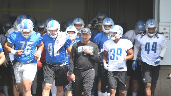 Detroit Lions head coach Jim Caldwell and the team head out to the field for the first day of Lions training camp.