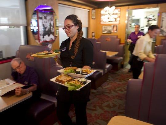 Aja Jones brings food to a table at Mel's Diner in