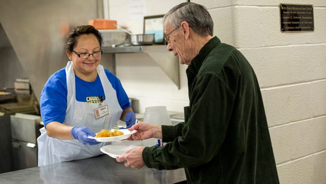 Volunteer Cheryl Pergande hands a plate of fried fish to Lyle Stevens, of Port Huron, during a Lent Fish Fry Friday, Feb. 19, 2016 at Our Lady of Guadalupe Hispanic Mission in Port Huron.