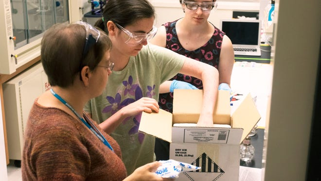 Stockton University professor Tara Luke (from left) and students Danielle Ertz of Woodlynne and Valkyrie Falciani of Hammonton pack their fungus experiment for its trip to the International Space Station. They are heading to Kennedy Space Center to watch the launch set there for  Monday.