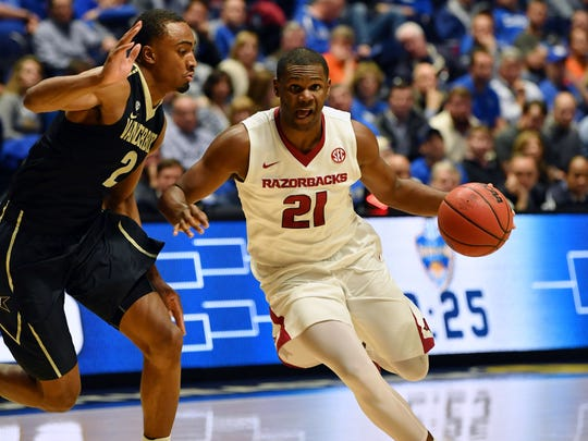 Arkansas guard Manuale Watkins (21) drives to the basket as he is defended by Vanderbilt guard Joe Toye (2) during the first half of an SEC Tournament semifinal on Saturday.
