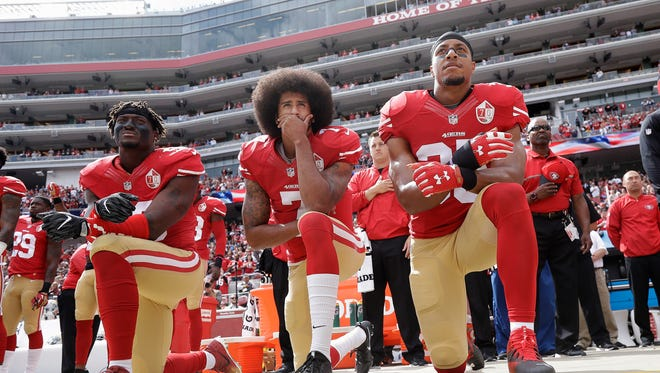 In this 2016 file photo, from left, San Francisco 49ers outside linebacker Eli Harold, quarterback Colin Kaepernick and safety Eric Reid kneel during the national anthem before an NFL football game against the Dallas Cowboys in Santa Clara, Calif.