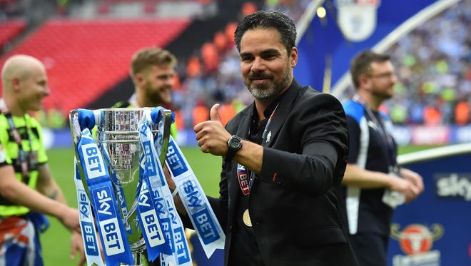 Coach David Wagner holds the Championship Playoff trophy after Huddersfield Town won the penalty shootout in the English Championship playoff.