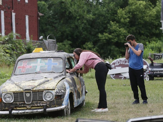 "Deanna Allos, 26, of Southfield takes a peek into a car that is painted and decorated by Tyree Guyton at his outdoor art installation, the Heidelberg Project Sunday, August 14, 2016 in Detroit on Heidelberg as her brother  Hadi Allos, 15, takes photos. This is their first time visiting and they had no idea that Guyton is dismantling his project and reconfiguring it. Their first impression of it is it is ""Cool"" and they had no idea it was a whole street."