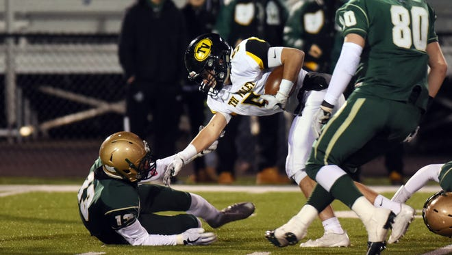 Chase Dinan runs through a defender after catching a pass during Tri-Valley's 24-6 win against Akron St. Vincent-St. Mary on Friday in a Division III state semifinal at Massillon Perry. Dinan has been one of the Scotties' key performers during their run to the state finals.