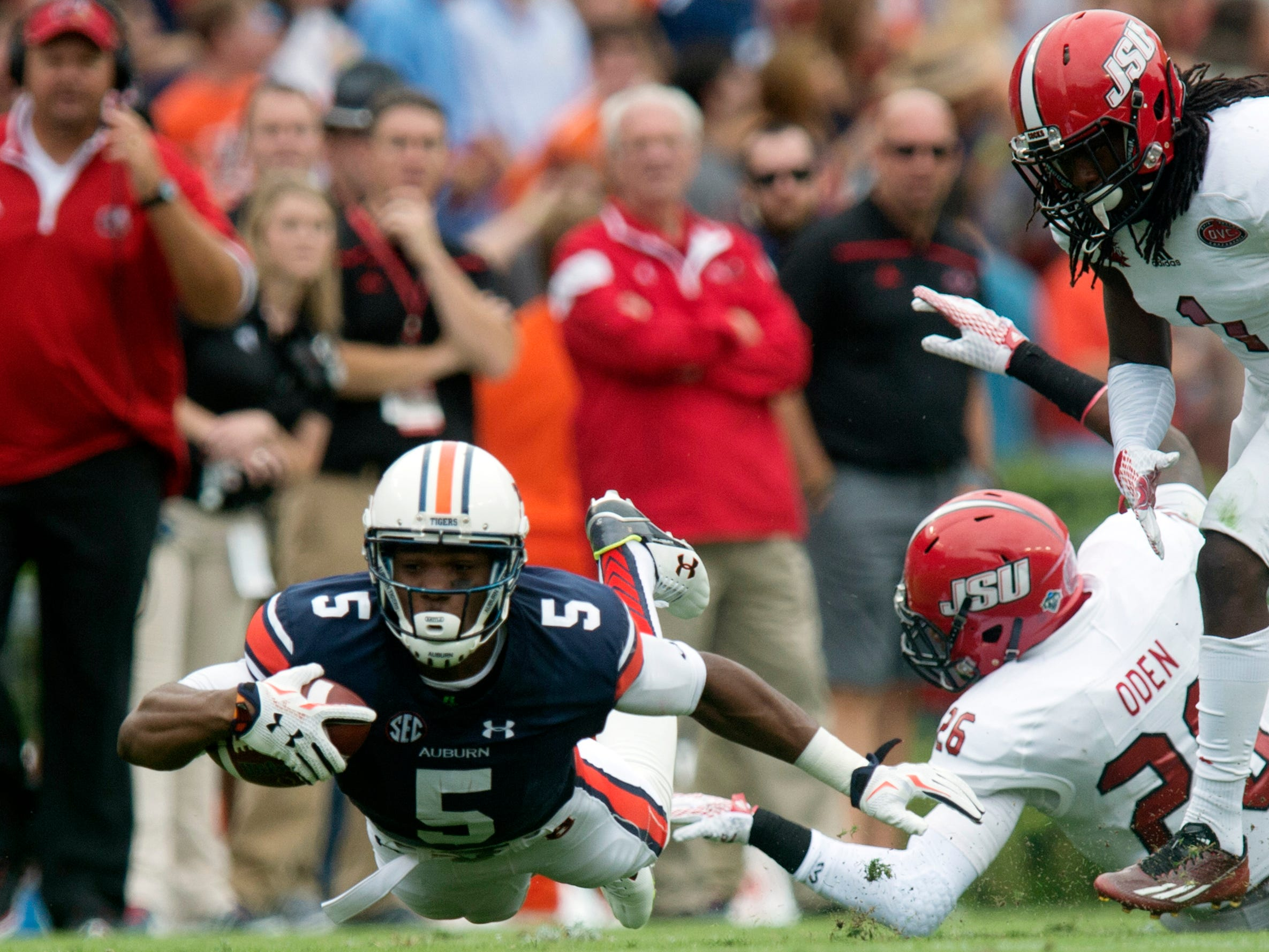 Auburn wide receiver Ricardo Louis (5) dives forward as Jacksonville State safety Santavious Oden (26) tackles him during the first half of an NCAA college football game, Saturday, Sept. 12, 2015, in at Jordan-Hare Stadium in Auburn, Ala. (Albert Cesare/The Montgomery Advertiser via AP) NO SALES; MANDATORY CREDIT