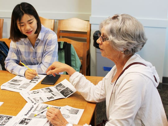 Alexandra Wong, left, listens to  Ocean County Library volunteer Christine Becauccio, who coordinates English Conversation Group sessions on Wednesday mornings at the Toms River Branch of the Ocean County Library. Wong has been attending the free sessions to become more familiar with the English language and American culture. She recently traveled to America from the China as part of a work study group.