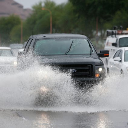 Vehicles drive through rain water running down McDowell Road on Wednesday, Sep. 17, 2014 in Phoenix, AZ. Storms are developing across the state as the remnants of Tropical Storm Odile. Flood watches are in effect across most of Arizona.