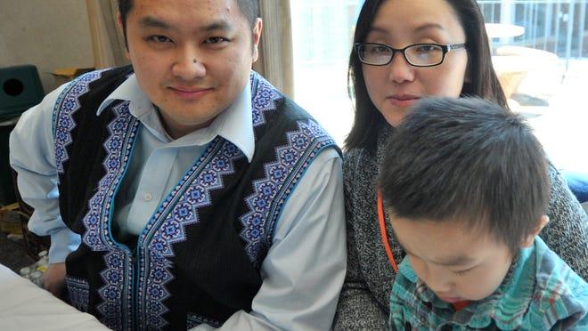 Keng Lee, his wife, Panhia, and 3-year-old son Peevxwm, all of Wausau, attended the University of Wisconsin Marathon County Cultural Festival last year. The festival was part of the Hmong Heritage Month celebration. ------------------------Keej Lis, nws tus pojniam Pajnyiag, thiab nkawv metub 3-xyoo Peevxwm, lawv nyob nroog Wausau, tabtom mus koom lub koobtsheej the University of Wisconsin Marathon County Cultural Festival xyoo tas los. Lub koobtsheej no yog ibqho ntawm Hmong Heritage Month.