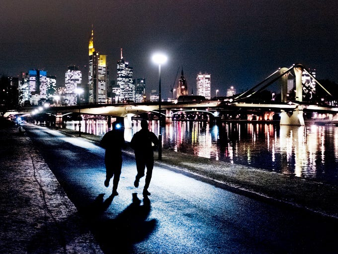 Two men run along the river Main with the buildings