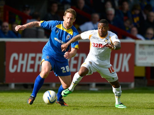 AFC Wimbledon player Darren Jones (left) battles Newton County player Aaron O'Connor during an April 18 soccer match in England. Indianapolis-based author John Green sponsors AFC Wimbledon with money earned on YouTube.
