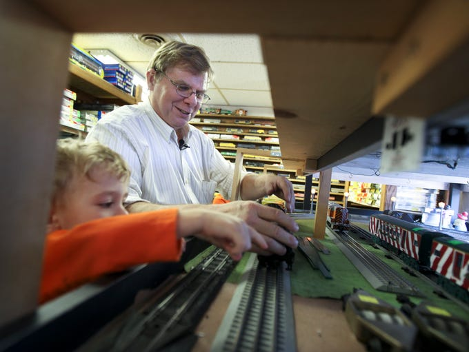 Roundhouse owner Kevin Cook works with Noah Howard, 2, who was in the store with his brother, Owen Howard, 4, and his grandparents. December 18, 2013