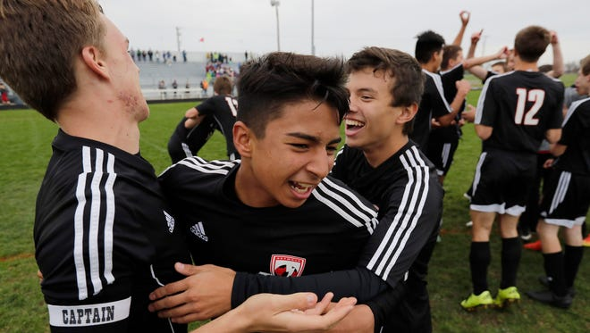 Seymour's Keven Sosa-Lassila (8) celebrates with Garrett Wendorff, right, and Oskar Petzold after Seymour defeated Fox Valley Lutheran in a D3 sectional final soccer match Saturday at Seymour High School.