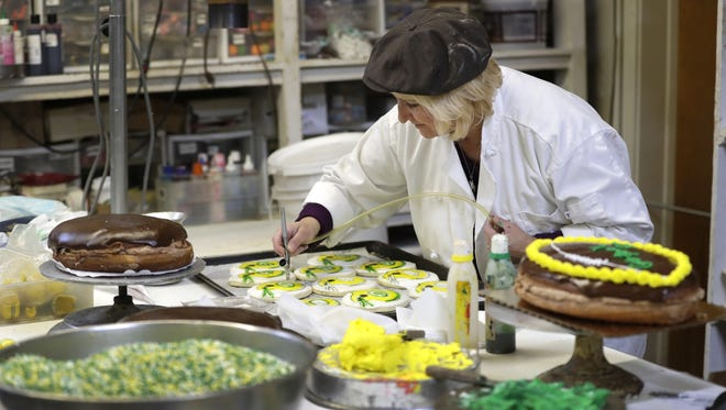 Hill top Barkery co-owner Lynn Engel air brushes Green Bay Packers themed sugar cookies Wednesday in Kaukauna.