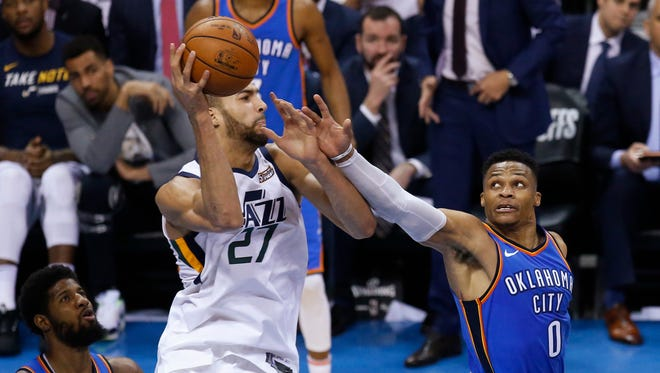 Utah Jazz center Rudy Gobert (27) grabs a rebound between Oklahoma City Thunder forward Paul George, left, and guard Russell Westbrook during the first half of Game 5 of an NBA basketball first-round playoff series in Oklahoma City, Wednesday, April 25, 2018.