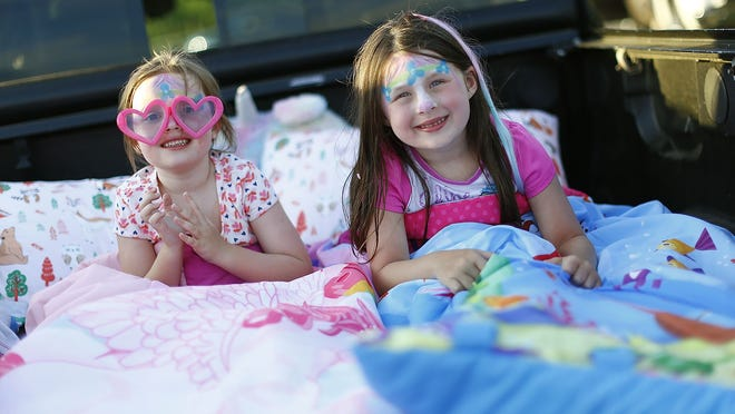 Leila Beatty, 5, and Ava Westervelt, 4, decked out with their Trolls face paint, are ready for the movie to begin during the pop up drive-in at the Marshfield Fairgrounds, which featured Trolls World Tour on Thursday, June 24, 2020. Greg Derr/The Patriot Ledger