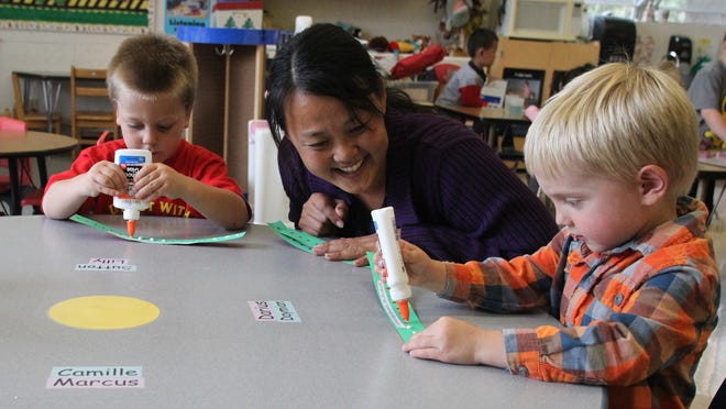 Teacher May Xiong helps Evan Cerny, right, and Devin Bahr with their glueing techniques in a 4-K class, Friday, September 16, 2011, at the A.C. Kiefer Educational Center in Wausau.