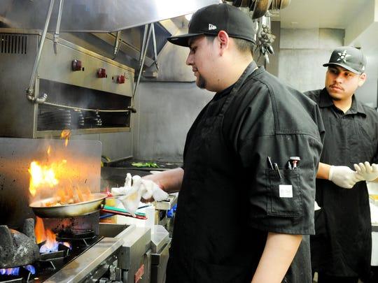 Chef Valente Ledezma makes Molcajete supremo as his assistant Elpidio Lopez makes pollo con mango at Qué Pasa! Mexican Cafe & Tequila Bar in Camarillo.