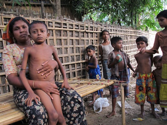 In this May 8, 2014, file photo, Salema Khatu, left wraps her arms around her son Habil, who was suffering from tuberculosis in an area for Rohingya refugees in north of Sittwe, western Rakhine state, Myanmar. Abdul Razak Ali Artan, the Somali-born student who carried out a car-and-knife attack at Ohio State University on Monday, reportedly railed on his Facebook account against U.S. interference in countries with Muslim communities. But he specifically protested the killing of Muslims in Myanmar _ also known as Burma _ where the Rohingya ethnic minority faces discrimination and occasional violence from the Buddhist majority and the army and bureaucracy. The Rohingya draw occasional international attention when the violence against them becomes too large to ignore, or when they seek foreign shores as boat people in great numbers, but their plight is generally ignored.