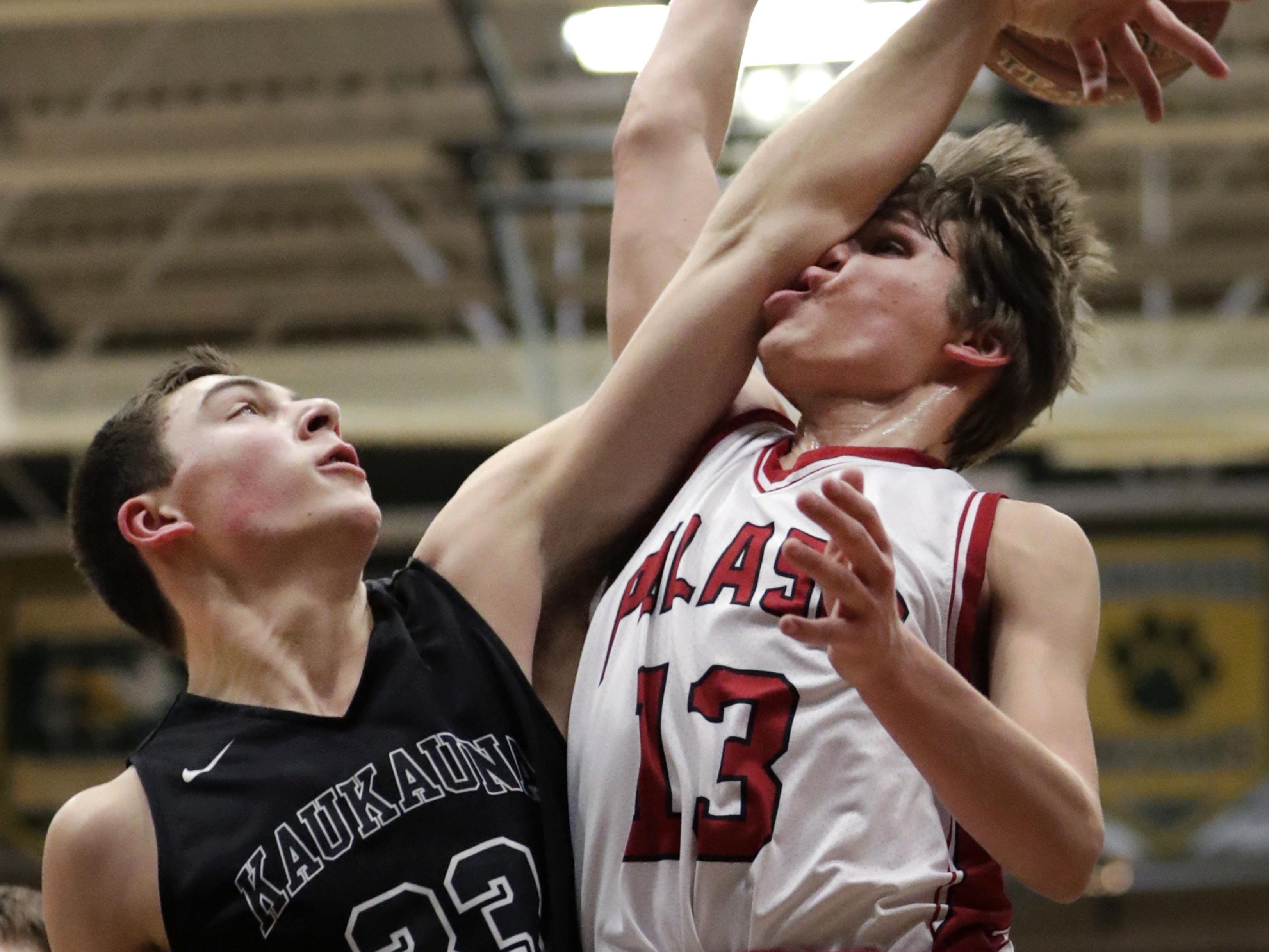 Kaukauna's Luke Eiting nails Pulaski's Trevor Stiede on a block attempt during Thursday's WIAA Division 2 boys sectional semifinal game at Ashwaubenon.